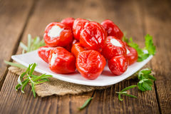 Portion of Red Pepper stuffed with cheese on wooden background. Fresh made Red Pepper stuffed with cheese on an old and rustic wooden table selective focus Royalty Free Stock Photos