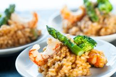 Portion of risotto rice with shrimps and asparagus. Stock Images