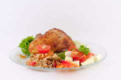 Portion of Roast Chicken. Leg with salad and rice on a white background royalty free stock photography