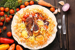 Portion of roasted chicken drumsticks with vegetables in a plate Stock Photos