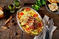 Portion of roasted lamb chops and saffron rice. Seasoned with fresh herbs and spices and served with roast vegetables in a top down view with ingredients on a stock photography