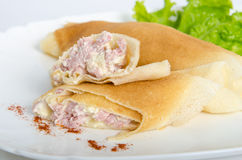 Portion of rolled pancakes or crepes cut in half stuffed with ham and cheese on oval dishes served  salad Royalty Free Stock Photography