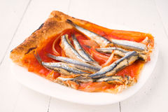 Portion of sardines baked on puff pastry on plate Stock Image