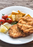 Portion of schnitzel with garnish. On the wooden table Stock Photo