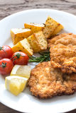 Portion of schnitzel with garnish. On the wooden table Stock Image