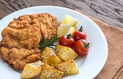 Portion of schnitzel with garnish. On the wooden table Stock Images