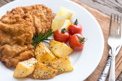 Portion of schnitzel with garnish. On the wooden table Royalty Free Stock Photos