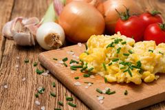 Portion of scrambled eggs with herbs on chopping board Stock Photography