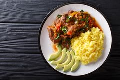 Portion of seco de chivo stewed goat meat with yellow rice and a. Vocado close-up on a plate on the table. horizontal top view from above stock image