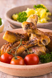 Portion of several chicken legs on plate in front of  potatoes and green salad Stock Photo