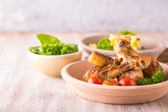 Portion of several chicken legs on plate in front of  potatoes and salad Royalty Free Stock Image