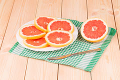Portion of sliced grapefruit on plate. Stock Photo