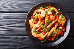 Portion of spicy shrimp with pepper, garlic, corn cob and herbs. Close-up on a plate. horizontal top view from above royalty free stock image