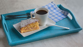 Portion sponge cake sprinkled with coconut  and coffee cup Royalty Free Stock Photography