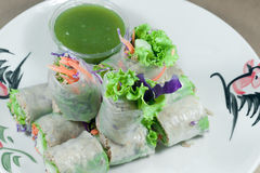 Portion of spring rolls on old wood with spicy sauce, vegetables Stock Images