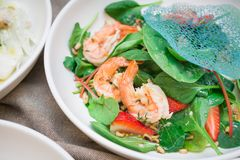 Portion of strawberry salad with leaves of fresh vegetables. And roasted pine nuts stock photo
