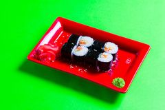 A portion of sushi on a red plate. green background.  royalty free stock photos