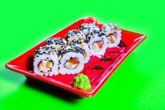 A portion of sushi on a red plate. green background.  stock image
