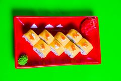 A portion of sushi on a red plate. green background. A portion of sushi on a red plate. green backgroun.d stock photos