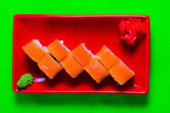 A portion of sushi on a red plate. green background.  royalty free stock photography