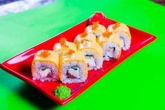 A portion of sushi on a red plate. green background. A portion of sushi on a red plate. green background stock photography