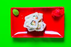 A portion of sushi on a red plate. green background. A portion of sushi on a red plate. green background stock image