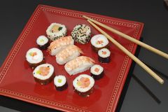 Appetizing  portion sushi. Portion sushi and wooden hopsticks on plate Royalty Free Stock Photos