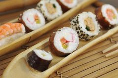 Appetizing  portion sushi. Portion sushi and wooden hopsticks on plate Royalty Free Stock Photography