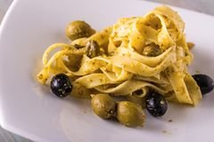 Portion of tagliatelle with green pesto and capers and olives Royalty Free Stock Images