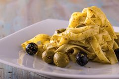Portion of tagliatelle with pesto and capers and olives Royalty Free Stock Photography