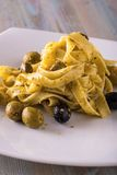 Portion of tagliatelle with pesto and olives Stock Photography