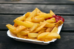 Portion of takeaway chips in a white container Stock Photos