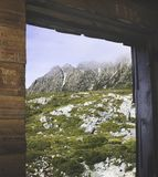 A portion of Tasmania`s Cradle Mountain is seen through a wooden doorway. A portion of Tasmania`s Cradle Mountain is seen through a graffitied wooden doorway royalty free stock images