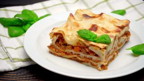 Portion of tasty lasagna on wooden backgound stock footage
