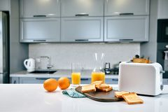 Portion of toasts on a wooden board with orange juice. Breakfast is served on a table with light blue napkin.