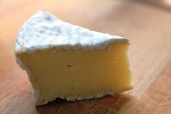 A slide of Camembert cheese. Portion of a typical French cheese, Camembert, with white rind. On a wooden plate. Camembert is a soft, creamy, surface-ripened cow` royalty free stock photography
