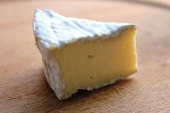 A slide of Camembert cheese. Portion of a typical French cheese, Camembert, with white rind. On a wooden plate. Camembert is a soft, creamy, surface-ripened cow` royalty free stock image