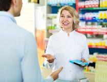 Portion utile de pharmacien et homme de consultation photographie stock libre de droits