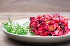 A portion of vinaigrette - a salad of boiled vegetables, sauerkraut and pickled cucumbers on a plate on a wooden table. National. Russian dish stock images