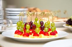 Portional canapes from grapes, strawberries and pineapple Royalty Free Stock Photos