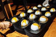 Portioner av glass som dekoreras med muttrar och frukt, täcker med sirap att tjänas som på en restaurang arkivfoton