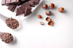 Portions and chocolate chips on container with hazelnuts isolate Stock Photo