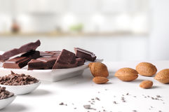 Portions and chocolate chips on containers with almonds in kitch Stock Image