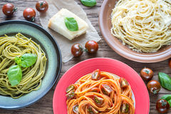 Portions of colorful spaghetti with ingredients stock photos
