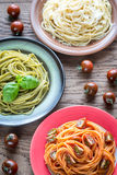 Portions of colorful spaghetti with ingredients royalty free stock images