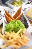 Portions of crumbed fried fish with potato chips. Portions of crumbed fried fish served with potato chips and fresh frilly green lettuce on newspaper in a royalty free stock photos