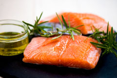 Portions of Fresh Raw Salmon Fillets with Aromatic Herbs and Oli. Portions of Fresh Raw Salmon Fillets with Aromatic Herbs and Spices and Olive Oil , Shallow DOF Royalty Free Stock Image
