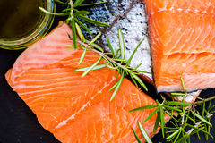 Portions of Fresh Raw Salmon Fillets with Aromatic Herbs and Oli. Portions of Fresh Raw Salmon Fillets with Aromatic Herbs and Spices and Olive Oil , Top View Royalty Free Stock Images