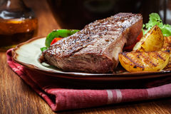 Portions of grilled beef steak with grilled potatoes and paprika Royalty Free Stock Image