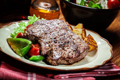 Portions of grilled beef steak with grilled potatoes and paprika Stock Images